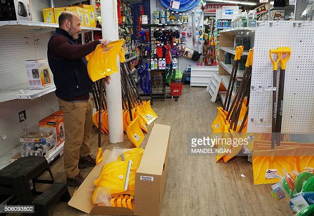 A worker in a hardware store assembles snow shovels on January 21 2016 ahead of an expected blizzard A blizzard warning has been issued for the...