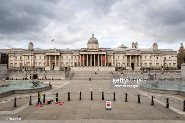 Worker in a hi-viz jacket waits by his tools in an almost deserted Trafalgar Square in London on March 20th, 2020. The centre of London is extremely...