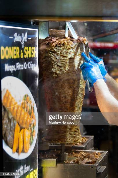 Worker in a kebab shop cuts kebab meat for a customer on March 16, 2019 in Cardiff, United Kingdom.