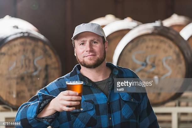 Travailleur dans une microbrasserie tenant un verre de bière