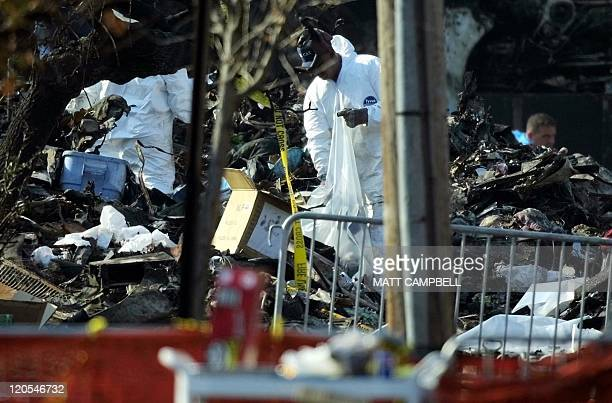 A worker in a protective suit retrieves items as he sifts through debris from the crash of American Airlines Flight 587 15 November 2001 in Queens...