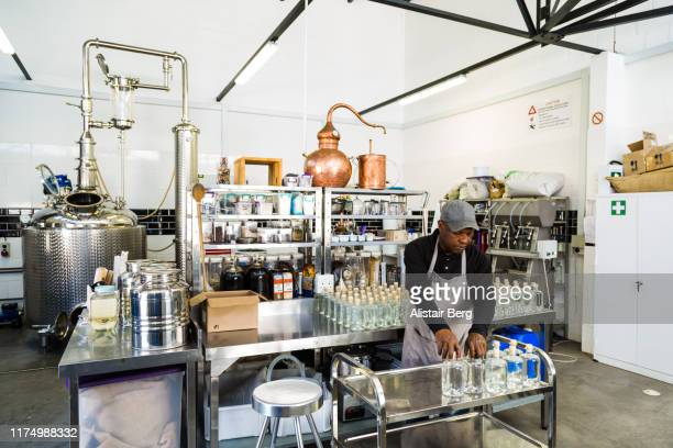 worker in a small scale gin distillery business - artisanal food and drink stock pictures, royalty-free photos & images