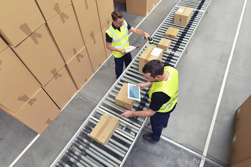 Worker in a warehouse in the logistics sector processing packages on the assembly line  - transport and processing of orders in trade 1066494754