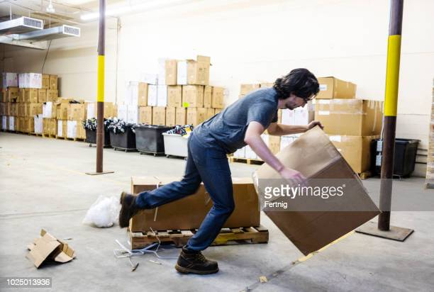 A worker in a warehouse tripping over a broken pallet