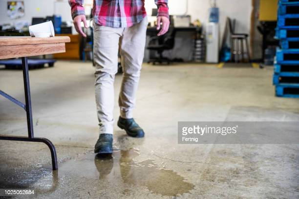 A worker in a warehouse walking in spilled liquid.