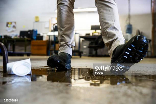 a worker in a warehouse walking in spilled liquid. - falling stock pictures, royalty-free photos & images