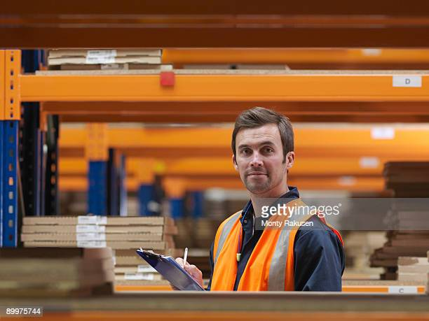 worker in aisle of warehouse - monty rakusen stock pictures, royalty-free photos & images