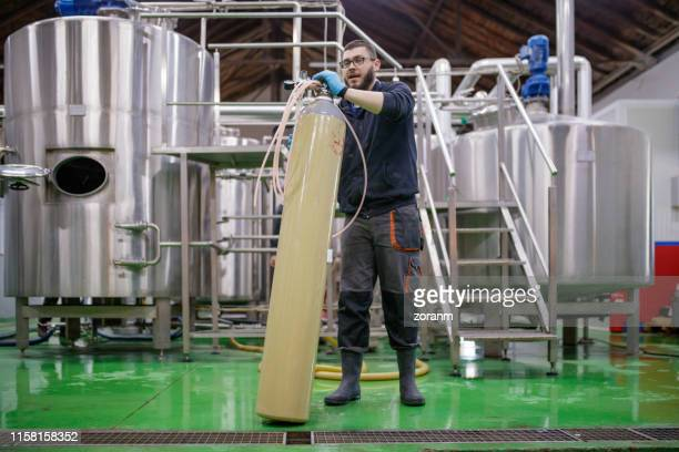 worker in brewery holding tall oxygen tank - cylinder stock pictures, royalty-free photos & images