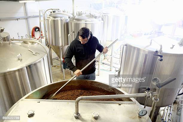 Worker in brewery, mixing barley grains in brew tank