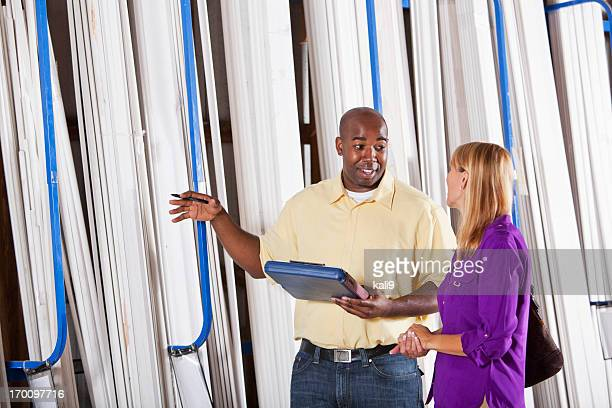 Worker in building supply store helping customer