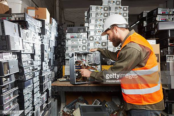 Worker in computer recycling plant dismounting desktop pc