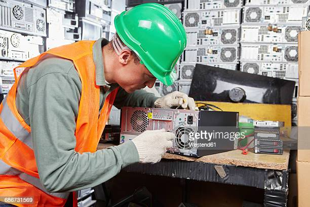 Worker in computer recycling plant opening pc casing