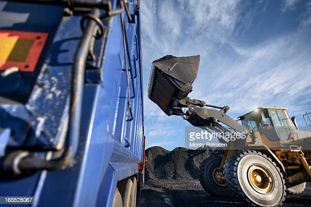 Worker in digger at coal loading station of surface coal mine