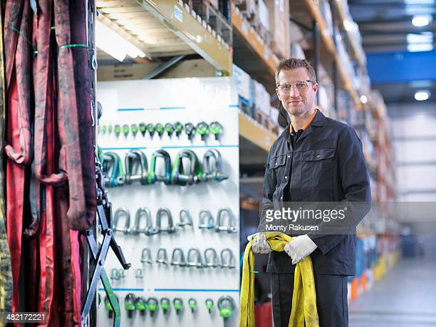 worker in engineering factory holding lifting gear, portrait - monty rakusen stock pictures, royalty-free photos & images