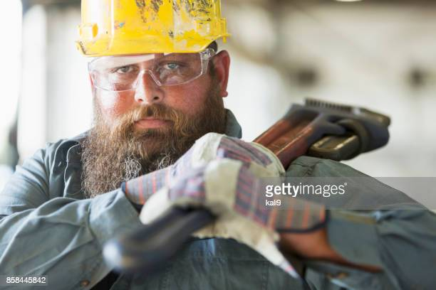 Worker in factory carrying work tool