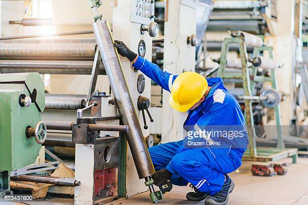 Worker in factory fixing roll bar for machine