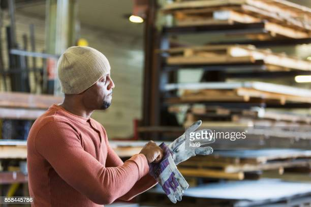 worker in factory putting on gloves - black glove stock pictures, royalty-free photos & images