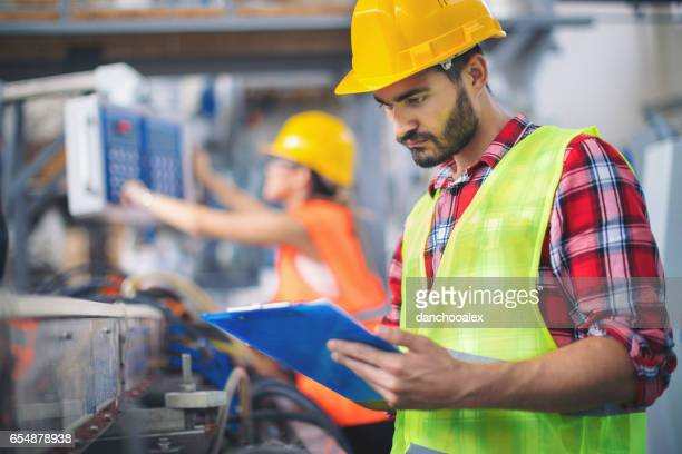 Worker in factory taking notes