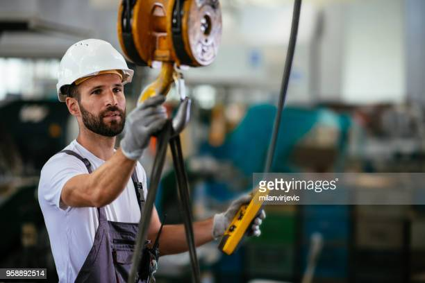 昇降ビームを用いた工場の労働者 - クレーン ストックフォトと画像
