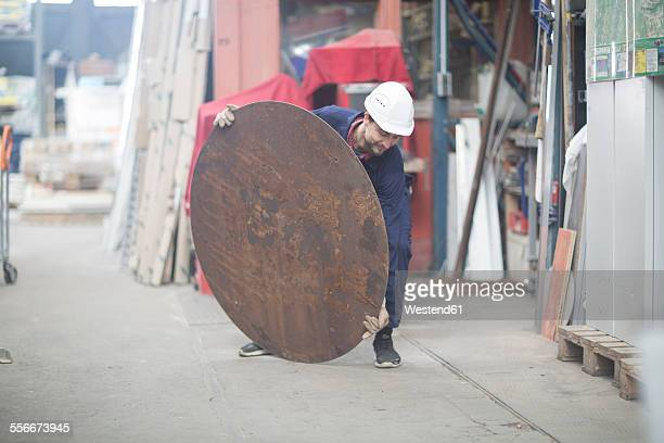 Worker in factory with metal plate