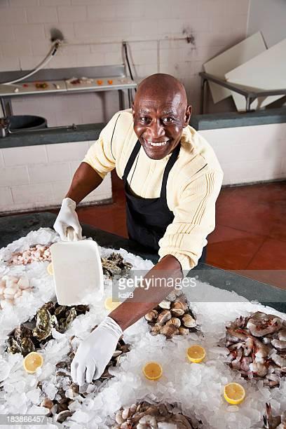 Worker in fish market arranging shellfish display