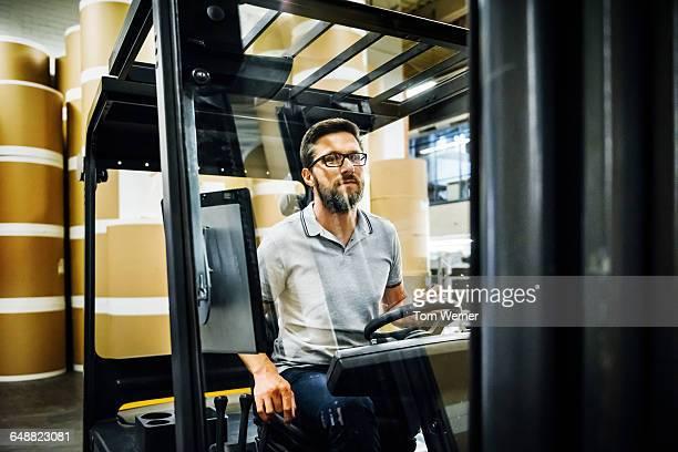 worker in forklift in a warehouse - gabelstapler stock-fotos und bilder