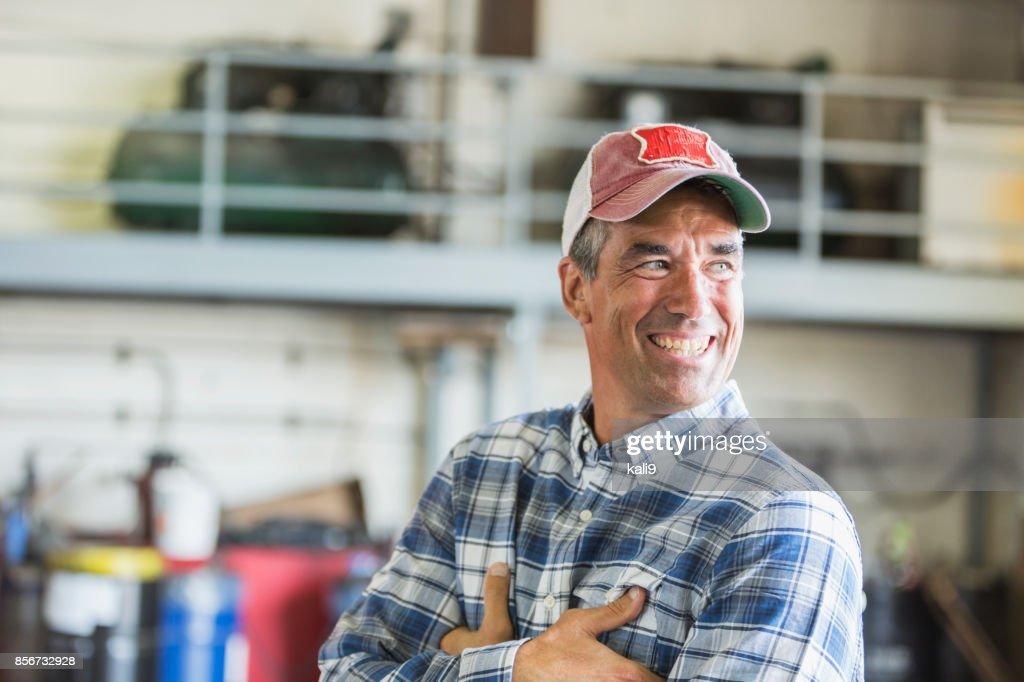 Worker in garage wearing trucker's hat : Stock Photo