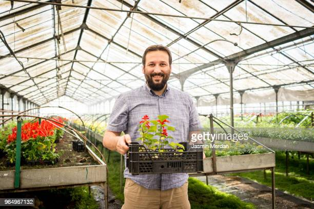 Worker in greenhouse with plants