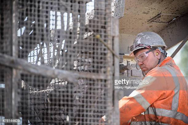 Worker in hard hat operating drilling rig in field