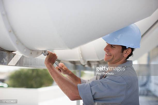 worker in hard-hat adjusting bolt on large pipe outdoors - tighten stock photos and pictures