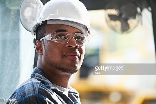 Trabalhador no capacete e óculos de segurança