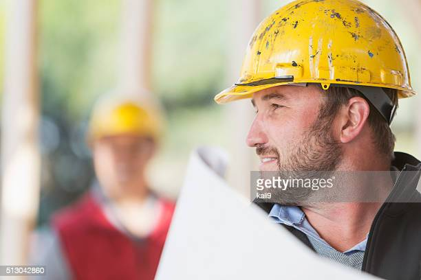 Worker in hardhat holding plans on construction site