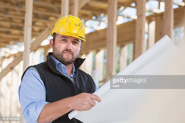 Worker in hardhat looking at plans on construction site