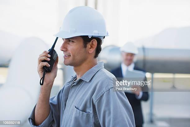 Worker in hard-hat talking on walkie-talkie outdoors