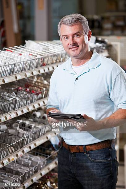 Worker in hardware store taking inventory