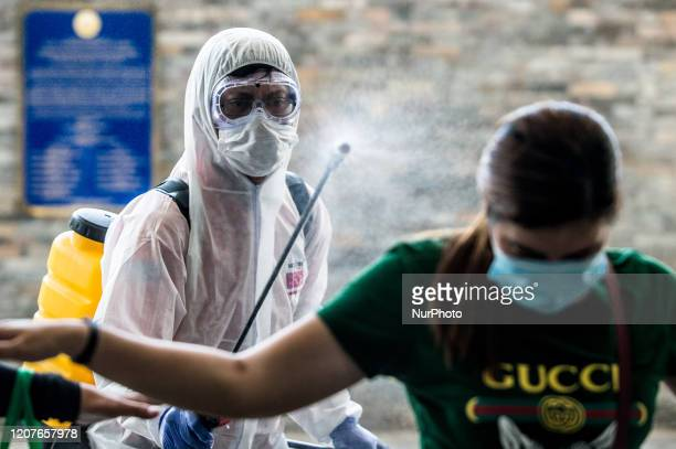 A worker in hazmat suit disinfects a woman in Pasig City Philippines on March 19 2020 The island of Luzon including Metro Manila is placed under an...