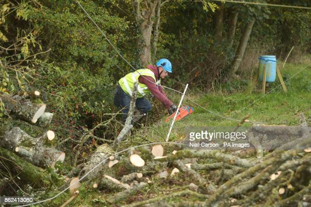 A worker in Kilcock Ireland clears fallen power lines after Hurricane Ophelia batterred the UK and Ireland with gusts of up to 80mph
