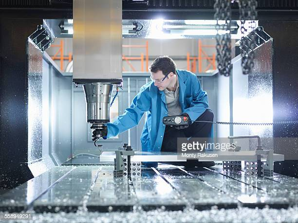 Worker in large CNC machine in plastics factory