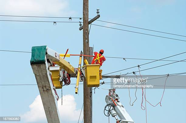 A worker in lift bucket repairs a street power pole