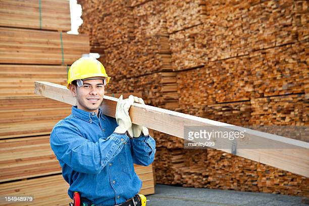 worker in lumber yard carrying 2x4