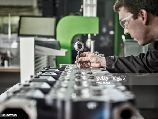 worker in metalworking factory controlling cylinder head - fabricage apparatuur stockfoto's en -beelden