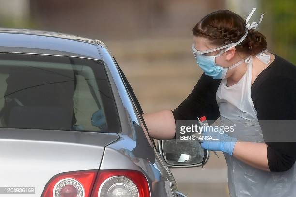 Worker in PPE including gloves, a face mask, eye protection and an apron, swabs an NHS worker at a drive-in facility to set up to test for the novel...