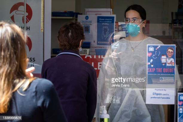 Worker in PPE takes orders from the front door a Pharmacy on September 08, 2021 in Narromine, Australia. New freedoms have been announced for fully...
