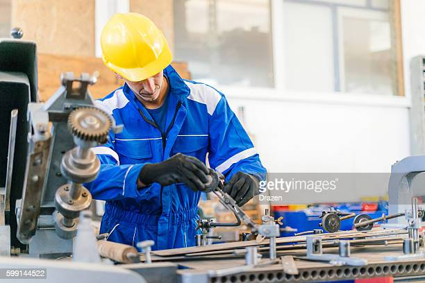 Worker in production line sets cog wheels