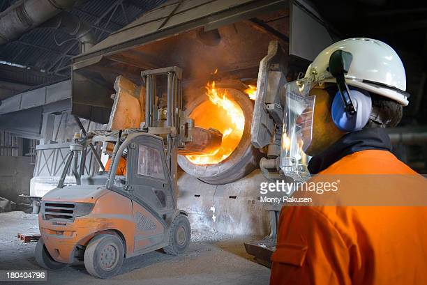 Worker in protective clothing watching forklift truck at furnace in aluminium foundry