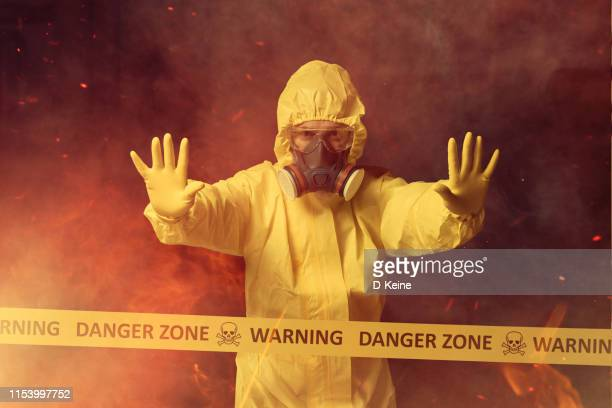 worker in protective suit showing stop gesture - hazmat stock pictures, royalty-free photos & images