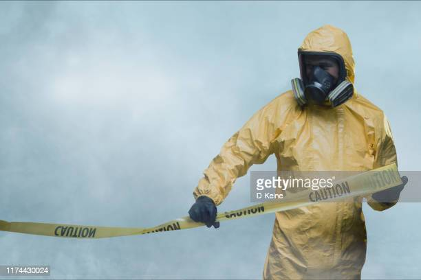 worker in protective suit with cordon tape - gas mask stock pictures, royalty-free photos & images