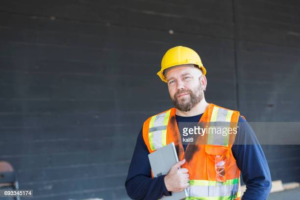 Werknemer in veiligheidsvest en veiligheidshelm holding digitale tablet
