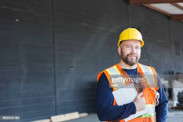 Worker in safety vest and hardhat holding digital tablet