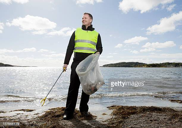 Worker in safety vest cleaning beach